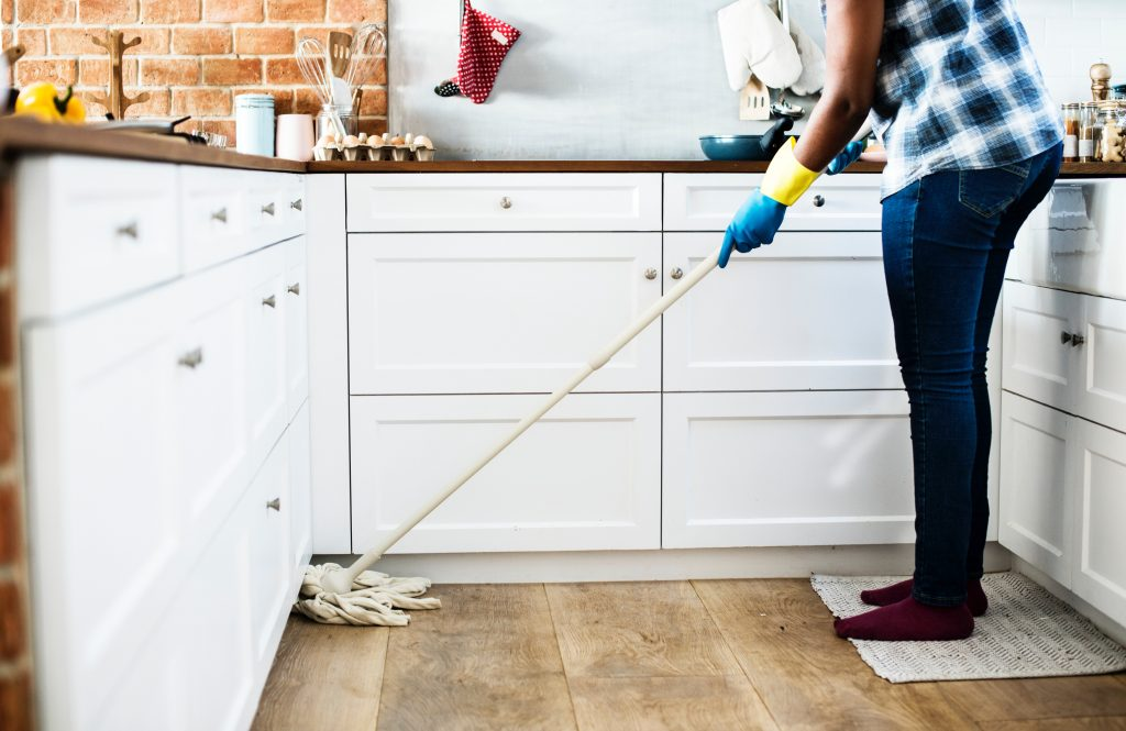 Picture of a person wearing rubber gloves mopping a kitchen floor
