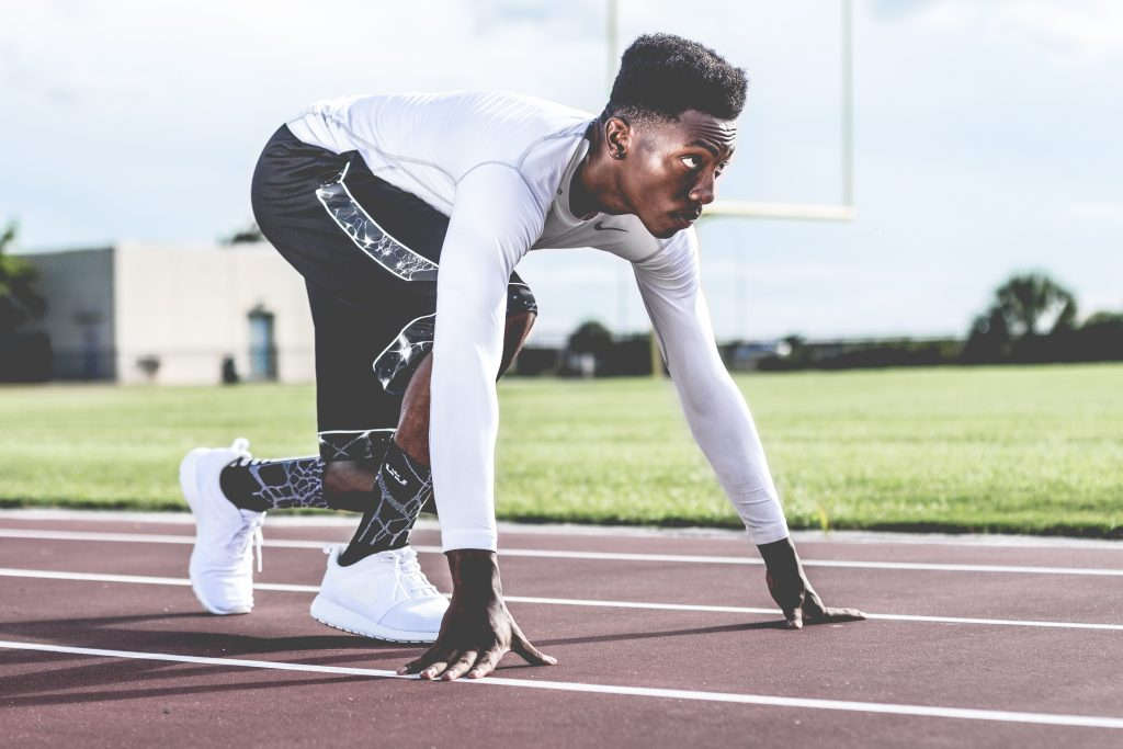 Picture of a man squat down on an athletic running track posed and ready to run